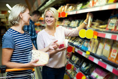 Adult girl with senior mother in cheese section of supermarket Royalty Free Stock Photos