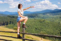 Adult girl standing on the fence. Over mountain landscape Royalty Free Stock Photography