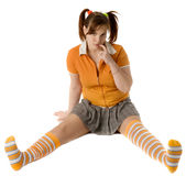 Adult girl with a two pony-tail sits on a floor Stock Photos