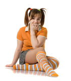 Adult girl with a two pony-tail sits on a floor Stock Photo