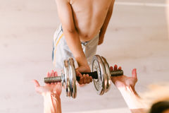 Adult gives the child a dumbbell. The boy takes a dumbbell from his mother Stock Photos
