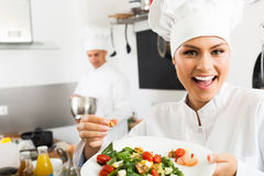 Adult glad female cook holding plate. Adult glad female cook wearing uniform holding plate with green salad Stock Photos