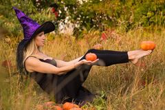 Adult glad girl in witch costume practicing yoga Stock Images