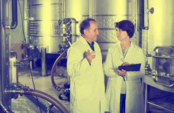 Adult glad wine maker shows to expert equipment Stock Photos