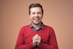 Adult good looking european man laughing, holding hands together and smiling broadly, having fun stock image