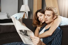 Adult good-looking people in relationship sitting spending morning together, reading newspaper and loving each other. He. Walked into her life and she do not Royalty Free Stock Photography