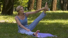 Adult gracefully demonstrating yoga poses in park, amateur workout, fitness. Stock footage stock footage