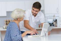 Adult grandson teaching grandma using computer Stock Images