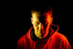 An adult guy stands with his head tilted down in an orange hooded sweatshirt highlighted in red and yellow on the sides with a royalty free stock images