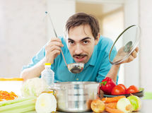 Adult guy tasting  vegetarian soup Stock Photography