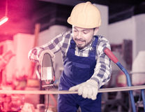 Adult guy is using power jigsaw for construction work Stock Photo