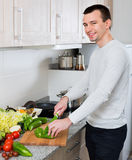 Adult guy with vegies in domestic kitchen Stock Photos