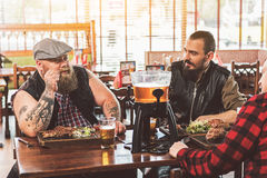 Adult guys resting in pub while having dinner stock photography