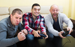 Adult guys sitting with joysticks Stock Image