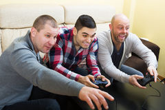 Adult guys sitting with joysticks Stock Photos