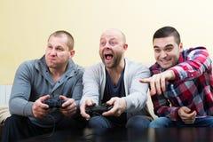 Adult guys sitting with joysticks Royalty Free Stock Photos