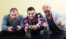 Adult guys sitting with joysticks Royalty Free Stock Photography