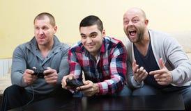 Adult guys sitting with joysticks Royalty Free Stock Image