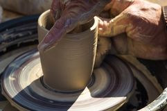 adult hand fed baby& x27;s hands to work with a potter& x27;s wheel Stock Photography