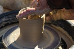 Adult hand fed baby`s hands to work with a potter`s wheel royalty free stock image