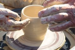 Adult hand fed baby`s hands to work with a potter`s wheel royalty free stock photography
