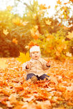Adult hand holds baby yellow autumn leafs at sunset Kid sitting, Royalty Free Stock Image