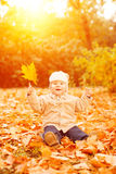Adult hand holds baby yellow autumn leafs at sunset Kid sitting, laughing and playing in a meadow on the nature walk outdoors. C royalty free stock photos