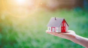 Free Adult Hand Is Holding Red House Model, Outdoors. Concept For New Home, Property And Estate Stock Photos - 165055283