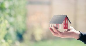 Free Adult Hand Is Holding Red House Model, Outdoors. Concept For New Home, Property And Estate. Text Space Stock Photo - 165054580