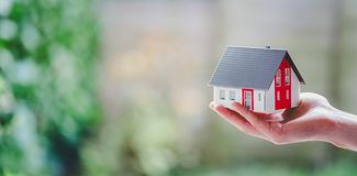 Free Adult Hand Is Holding Red House Model, Outdoors. Concept For New Home, Property And Estate. Text Space Stock Image - 165054661