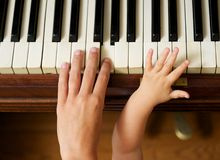 Adult hand playing piano with baby hand Stock Photos