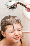 Adult hand washing a small child in the shower Stock Images