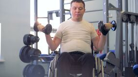 An adult handicapped man keeps lifting dumb-bells after a brief pause. 4K stock video footage