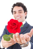 Adult handsome smiling man in a suit holding a red rose and offe Stock Photos