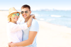 Adult happy couple hugging at the beach. A picture of a young romantic couple hugging at the beach and copy space Royalty Free Stock Image