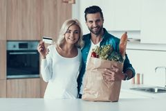 Adult happy couple is standing in kitchen with package of products. Consumerism concept. Credit card payment Stock Images