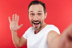 Adult happy man make selfie. Portrait of an adult happy man standing  over red background looking camera make selfie Royalty Free Stock Photos