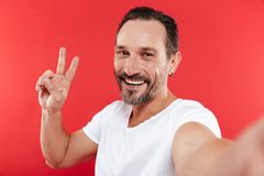 Adult happy man make selfie showing peace gesture. Portrait of an adult happy man standing  over red background looking camera make selfie showing peace gesture Royalty Free Stock Photo