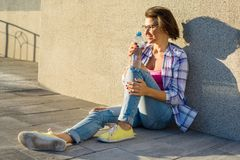 Adult healthy woman drinks water from bottle. Outdoor portrait Stock Photos