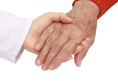 Adult helping senior in hospital stock images
