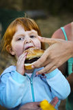 Adult Helping Young Child With Hamburger. Young girl eating hamburger, with adult hands reaching in to help. Vertically framed shot Royalty Free Stock Image