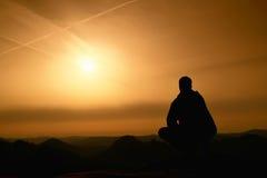 Adult hiker in black sit on mountain  edge. Man enjoying evening Royalty Free Stock Images