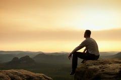 Adult hiker in black sit on mountain  edge. Man enjoying evening Stock Image