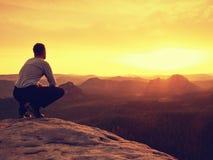 Adult hiker in black sit on mountain  edge. Man enjoying evening Royalty Free Stock Photo