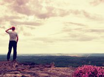 Adult hiker on the cliff in rocky mountains park and watch into countryside Royalty Free Stock Photography