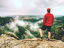 Adult hiker in red shirt and dark running pants. Tall man stock image