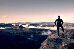 Adult hiker stand on cliff of sandstone empires park and watching over the misty and foggy morning valley Royalty Free Stock Photos