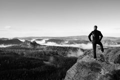 Adult hiker stand on cliff of sandstone empires park and watching over the misty and foggy morning valley Stock Images