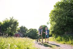An adult hipster son with bicycle and senior father walking in sunny nature. An adult hipster son with bicycle and senior father walking on a road in sunny stock photos