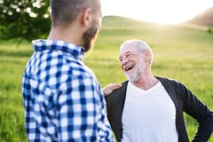 An adult hipster son with senior father on a walk in nature at sunset. An adult hipster son with his senior father on a walk in nature at sunset Royalty Free Stock Images